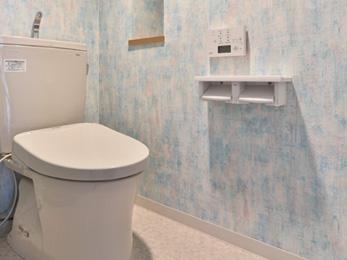 ペイントしたような淡いブルーが基調のクロスを貼り、爽やかな印象にまとめたトイレ