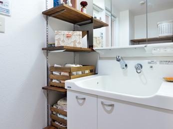 洗面化粧台の横にはオープンタイプの可動棚を造作で取り付けた