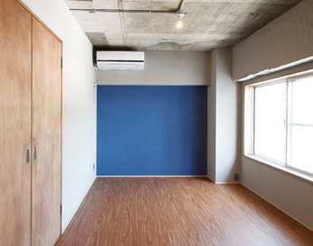 寝室の壁の一面にだけネイビーカラーの塗装を施し、鮮やかな彩りをプラス